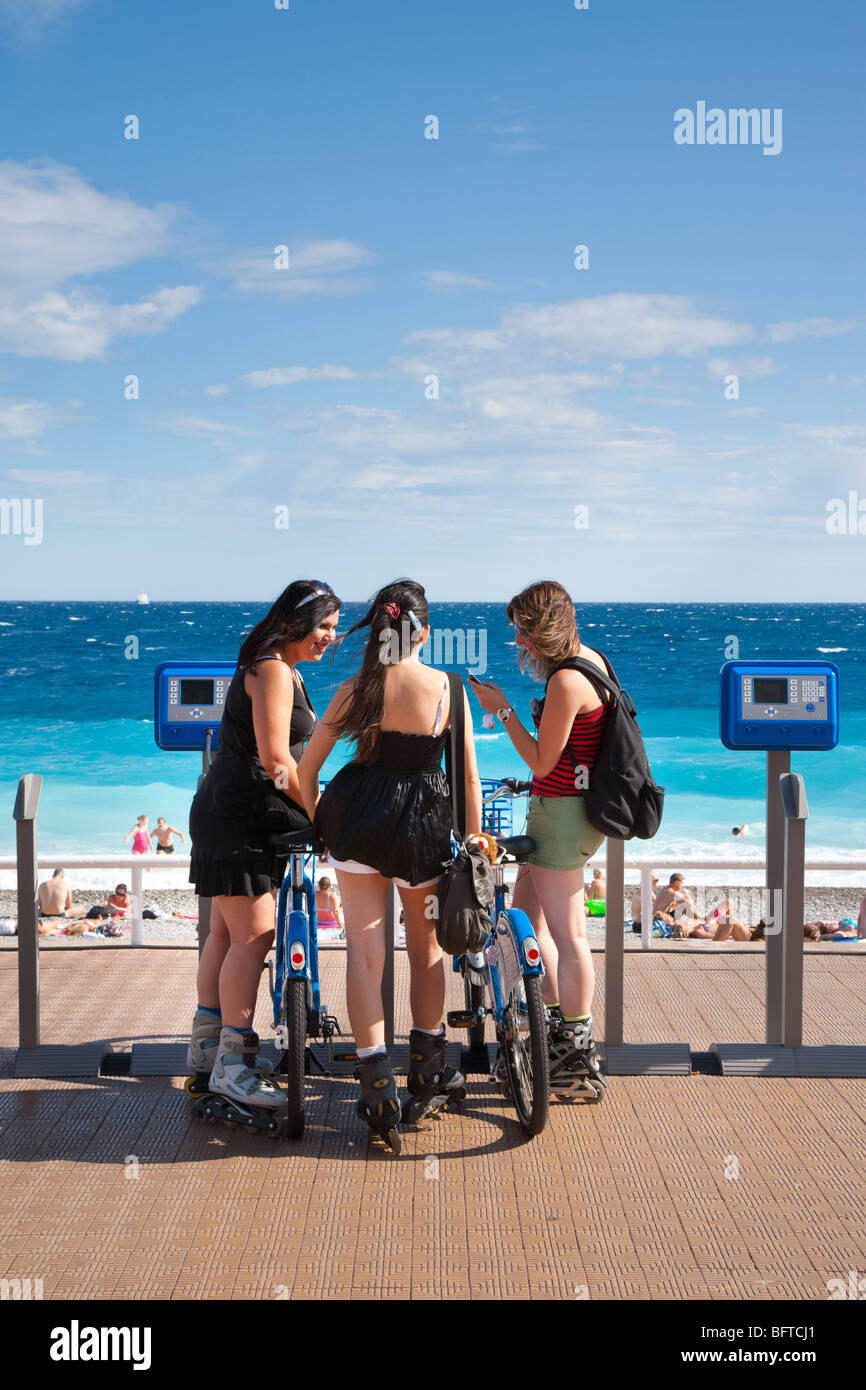 Teenage girls on rollerblades beside bicycles on the Promenade des Anglais, Nice, Provence, France Stock Photo
