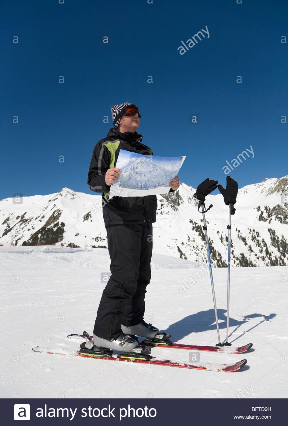 Man reading map on ski slope - Stock Image