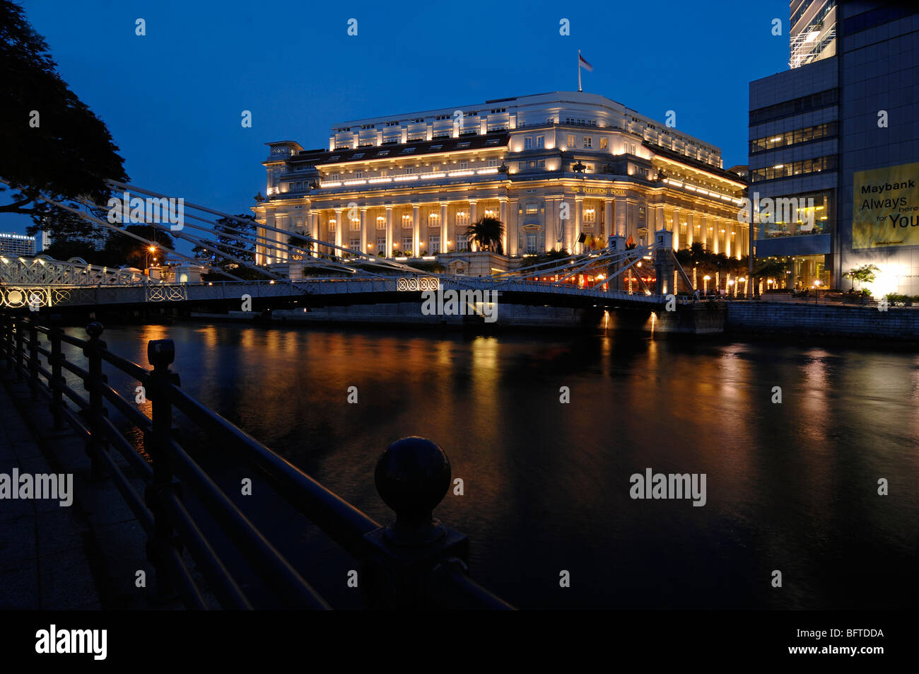 The Luxury Up-Market Fullerton Hotel (former the Central Post Office) Lit at Night & the Singapore River, Singapore - Stock Image