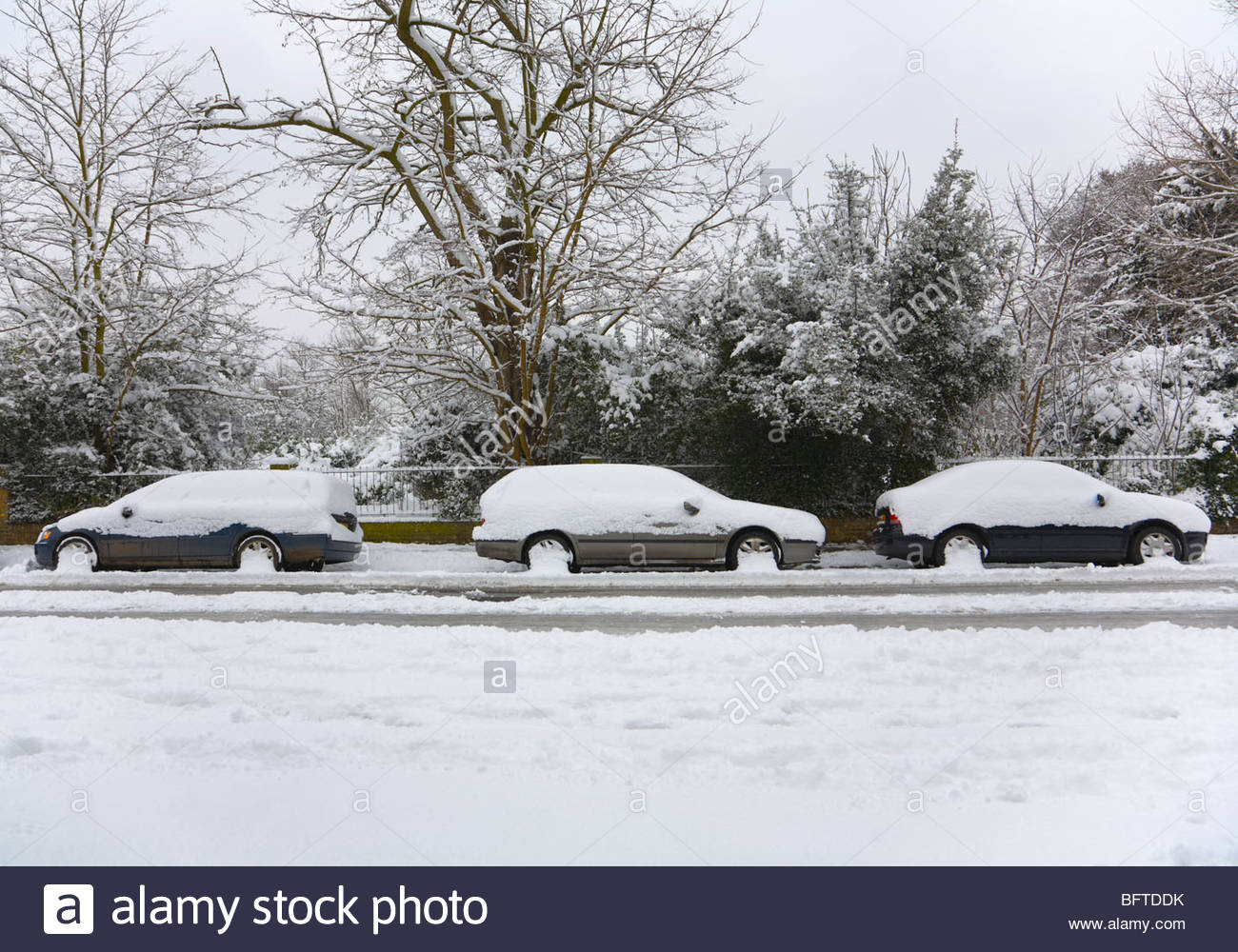 Three snow covered cars parked - Stock Image