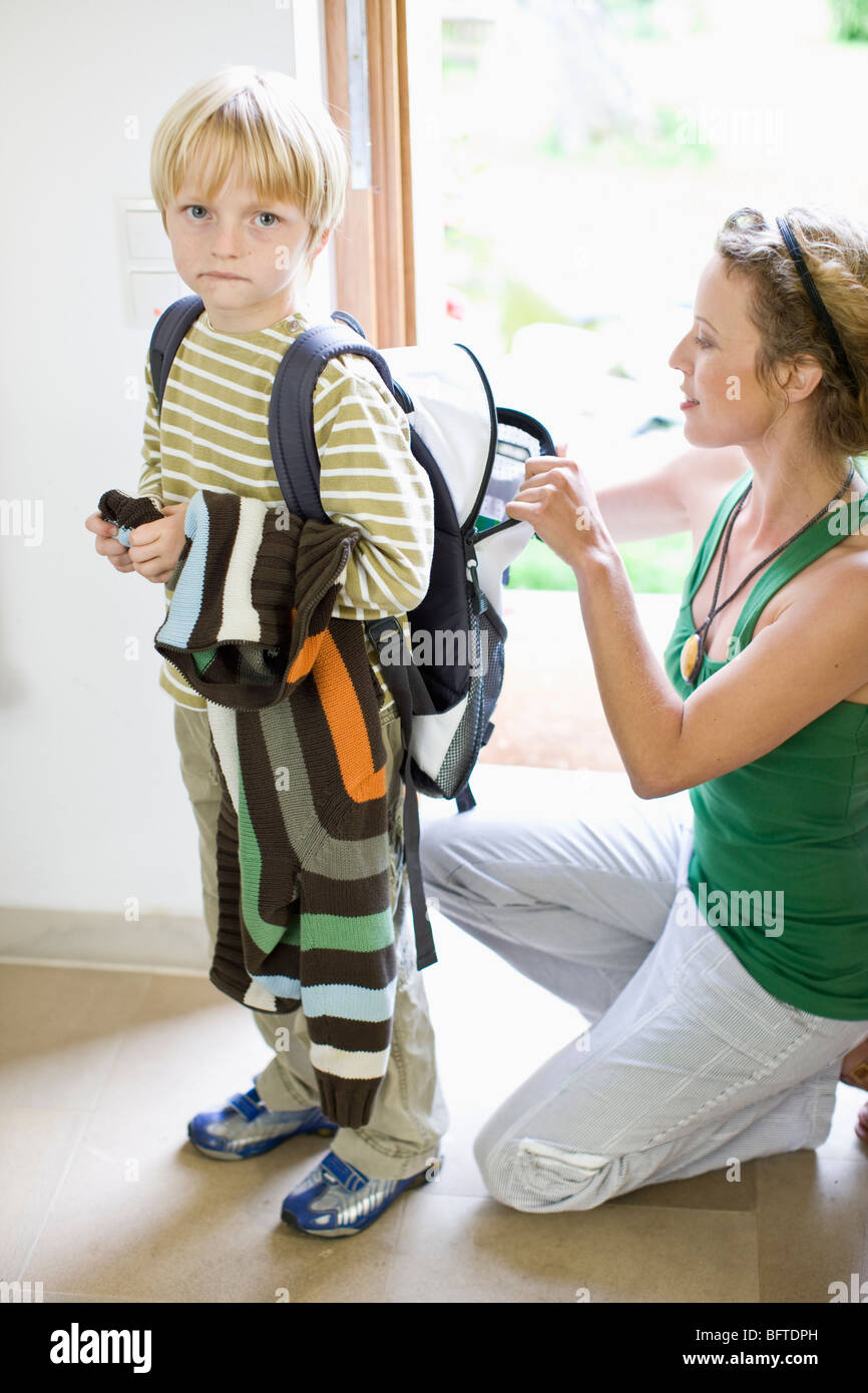 mother getting her son ready for school - Stock Image