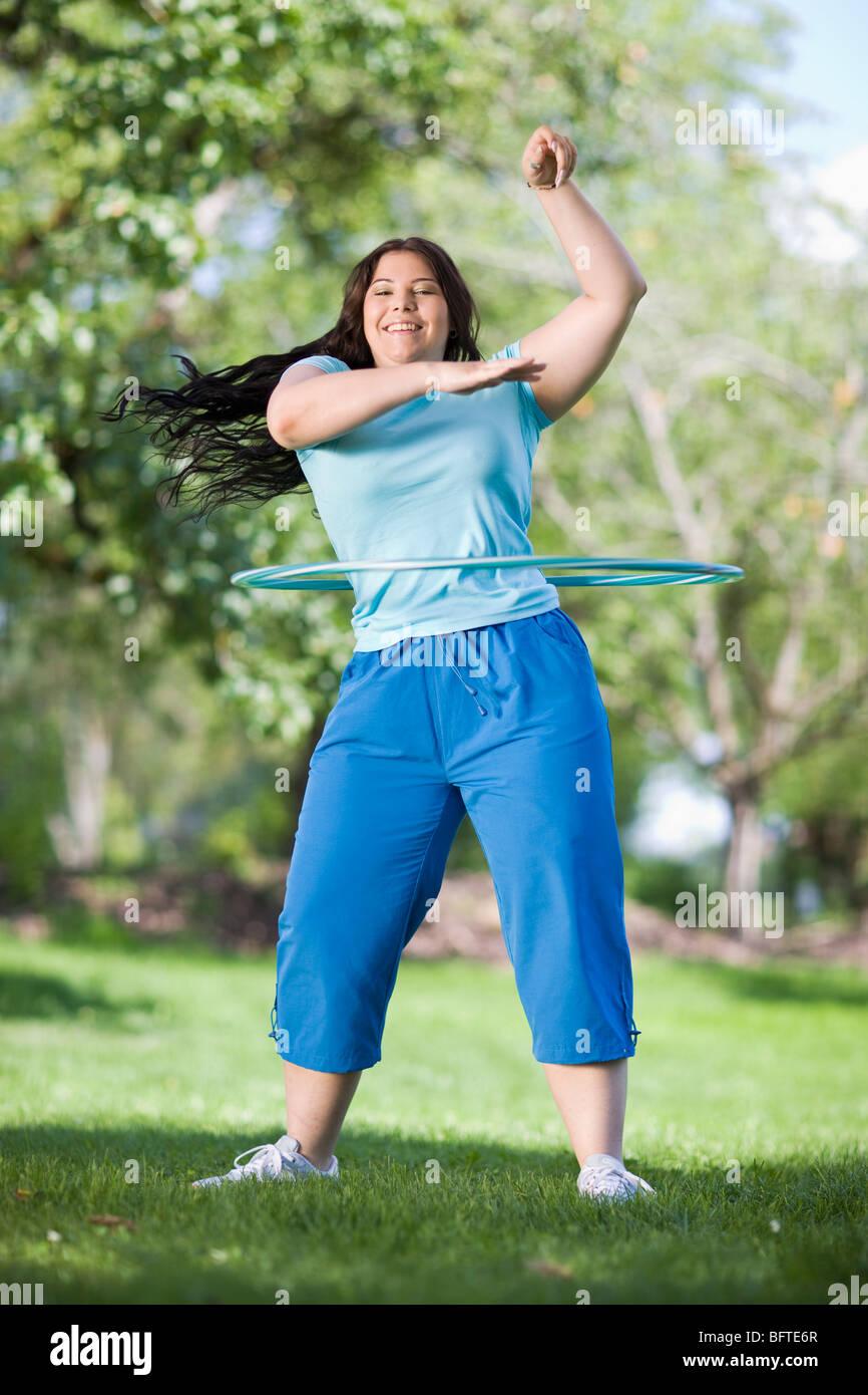 young plump girl doing hula hoop - Stock Image