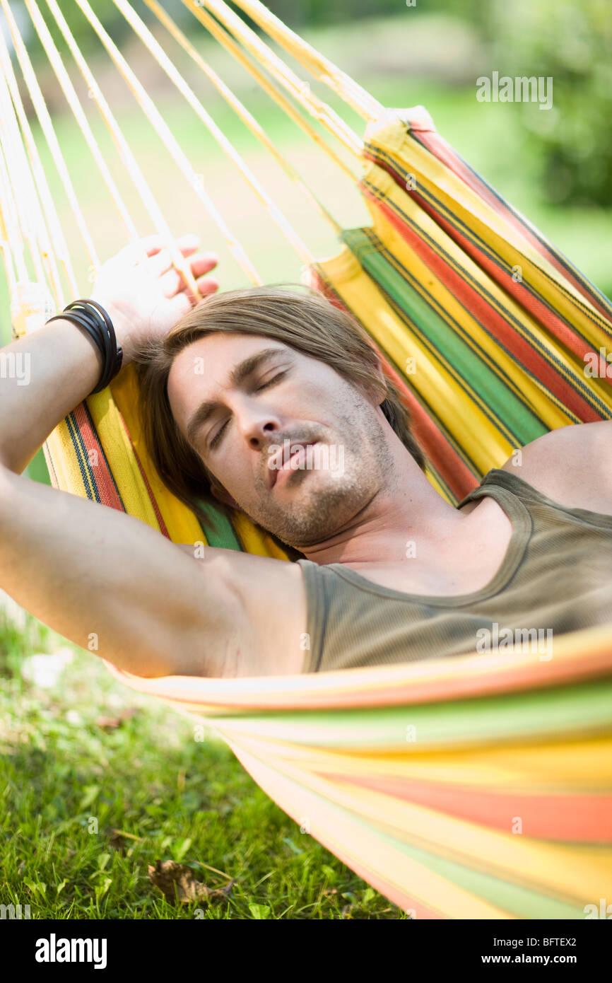 Man sleeping in a hammock - Stock Image