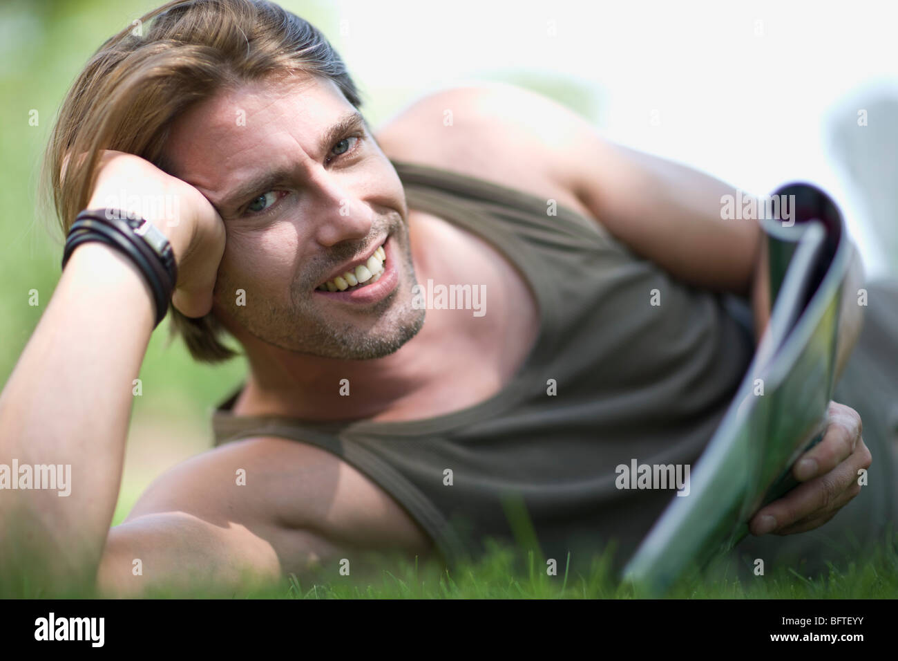 man lying in the lawn - Stock Image