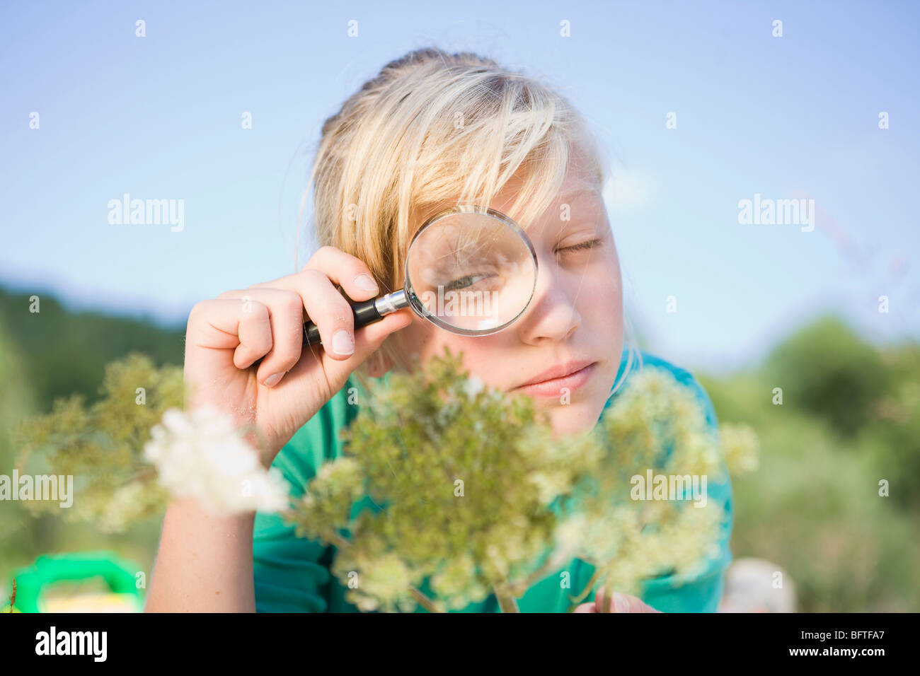 girl examines a flower - Stock Image