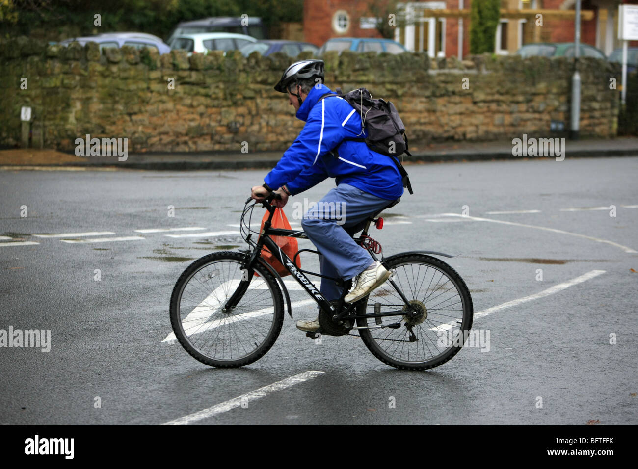 Adult male dressed in wet weather gear riding his bicycle in the rain - Stock Image