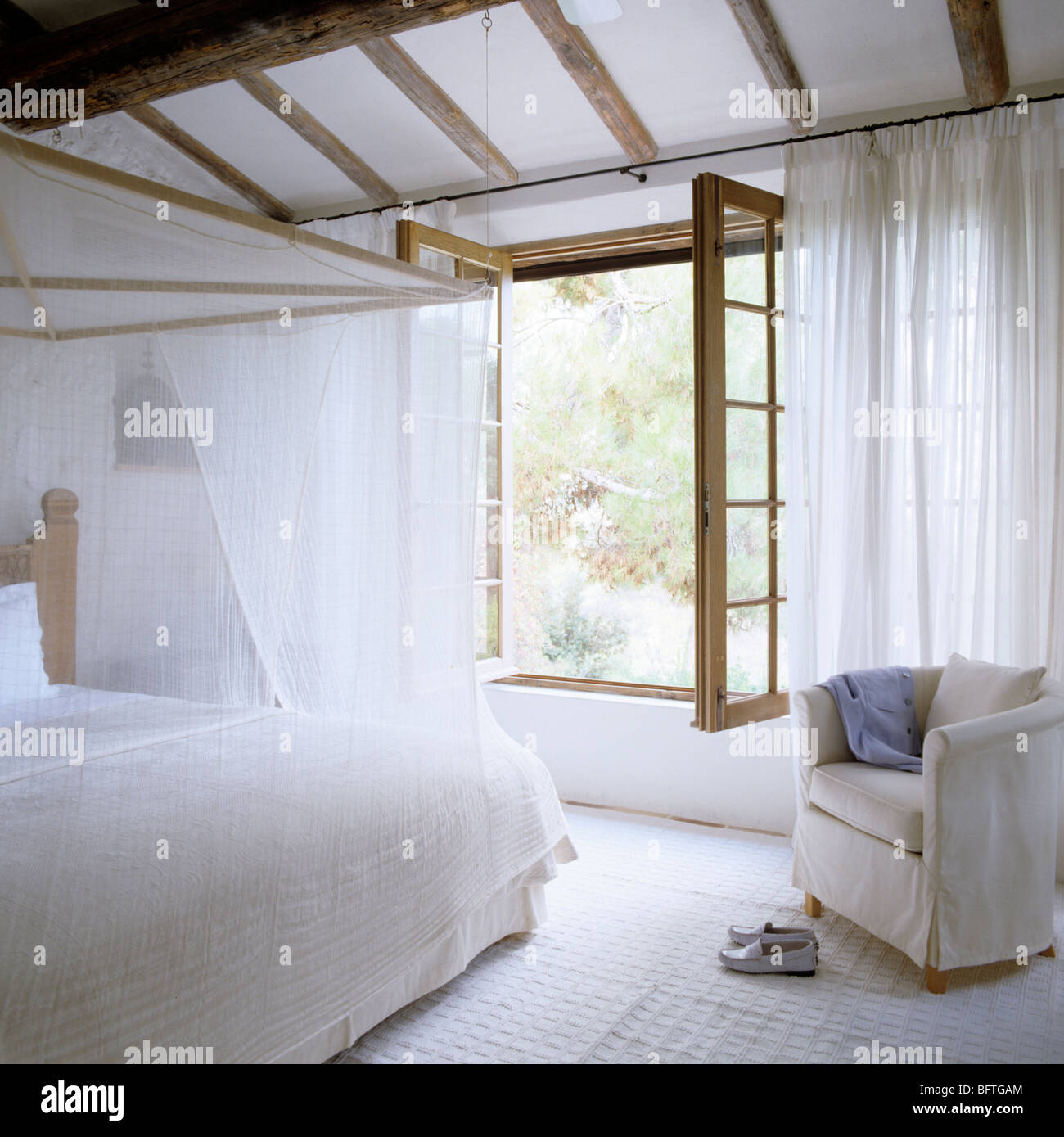 Bedroom With Open Windows White Curtains And Muslin Bed Cover