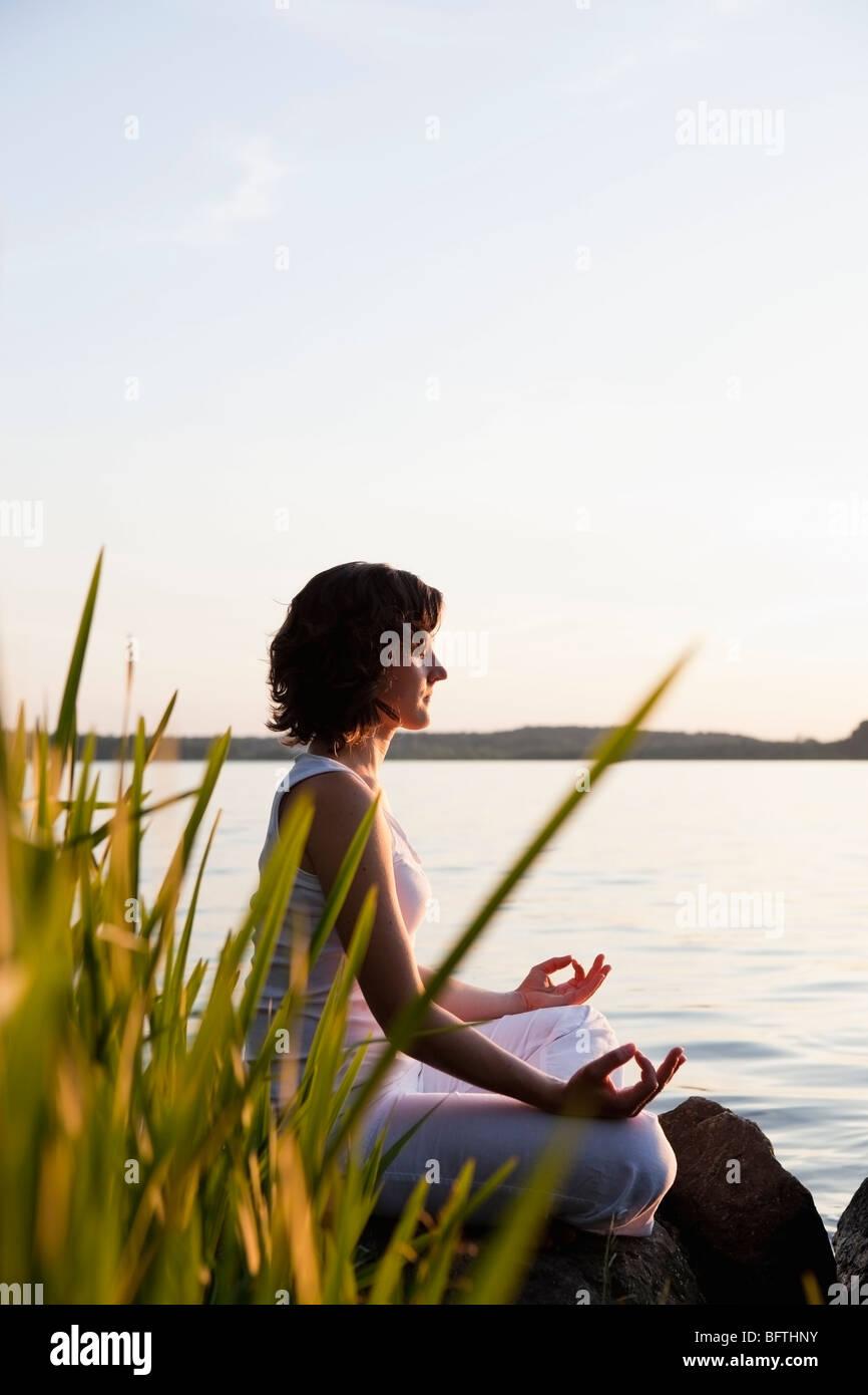 Woman Doing Yoga At Lakeside - Stock Image
