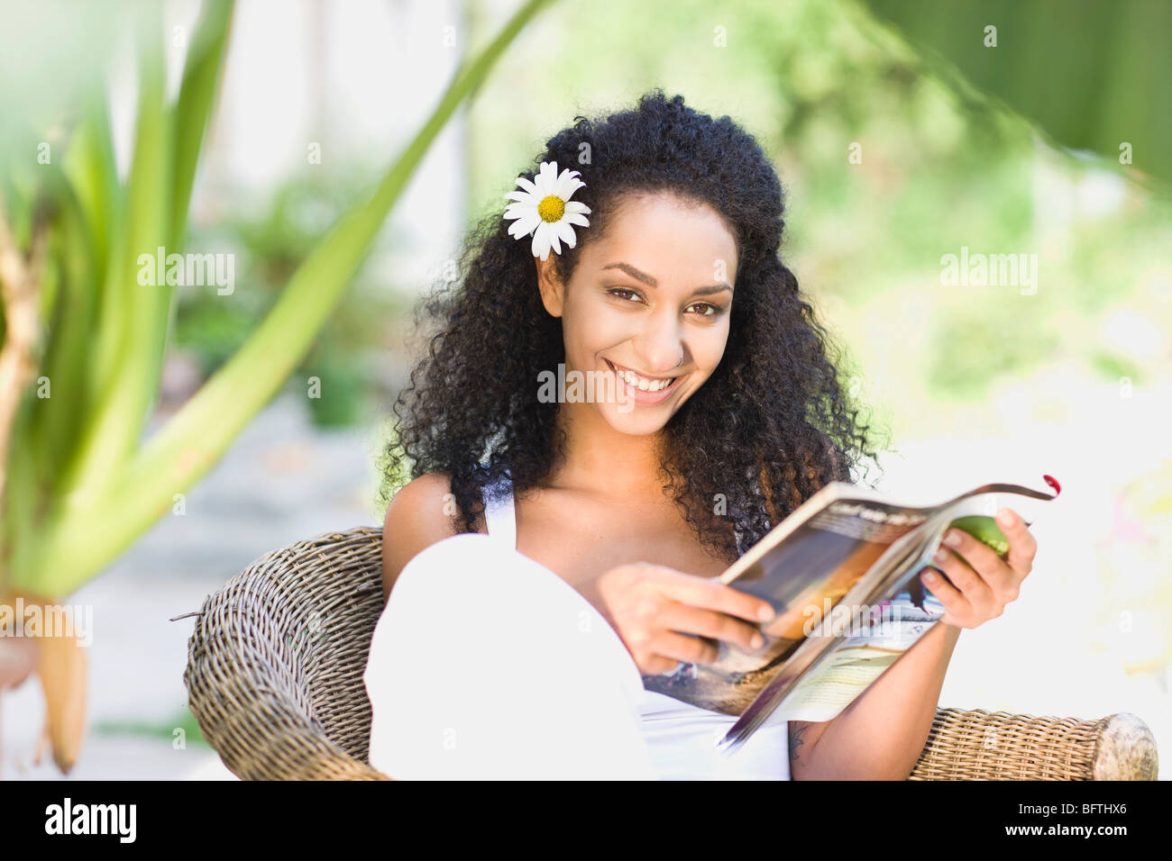 woman sitting in a garden chair - Stock Image