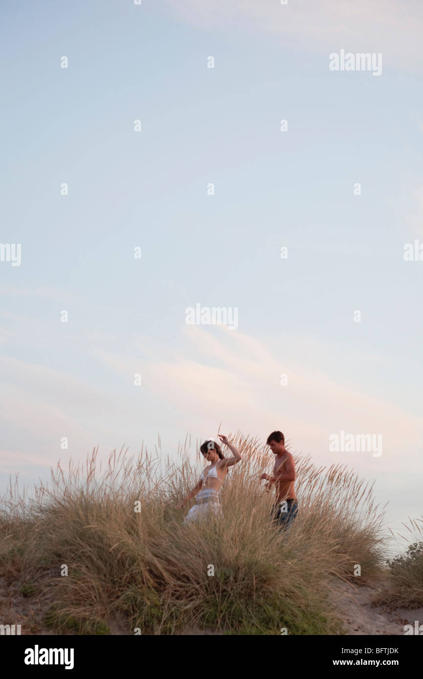 couple playing in the reed at the beach - Stock Image