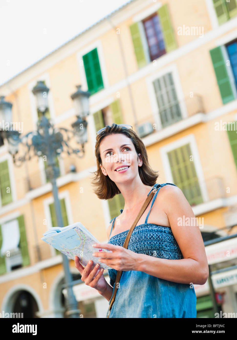 woman holding map looking around - Stock Image