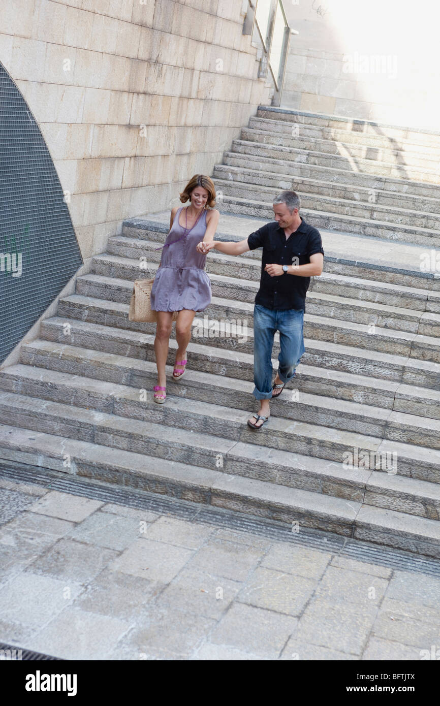 couple running down stairs - Stock Image