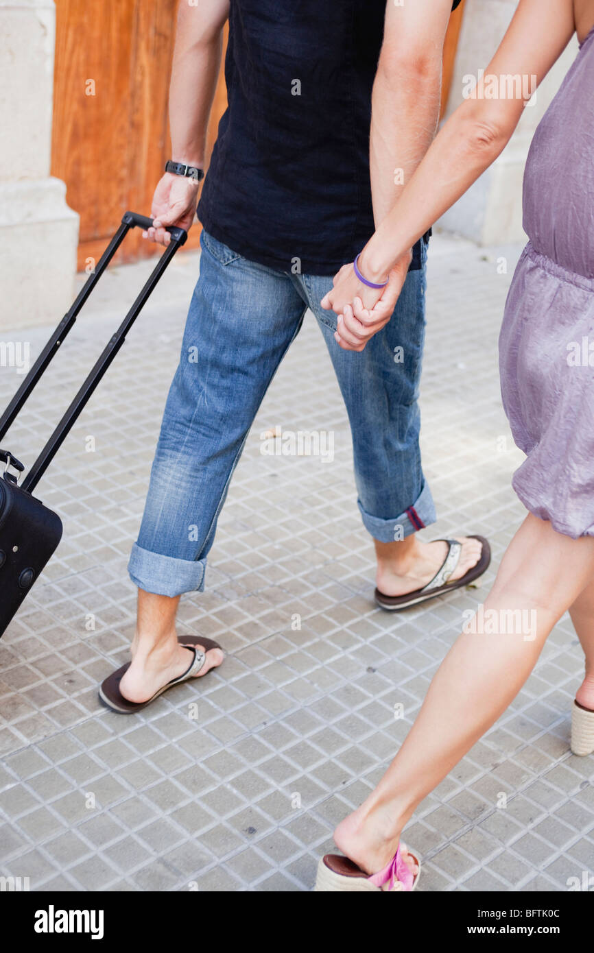 couple with trolly walking along street Stock Photo