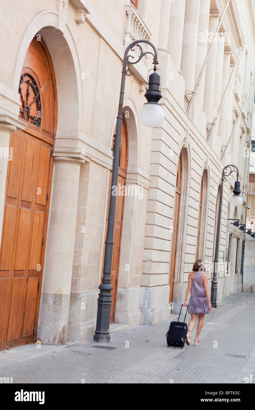 woman with trolly walking along street Stock Photo