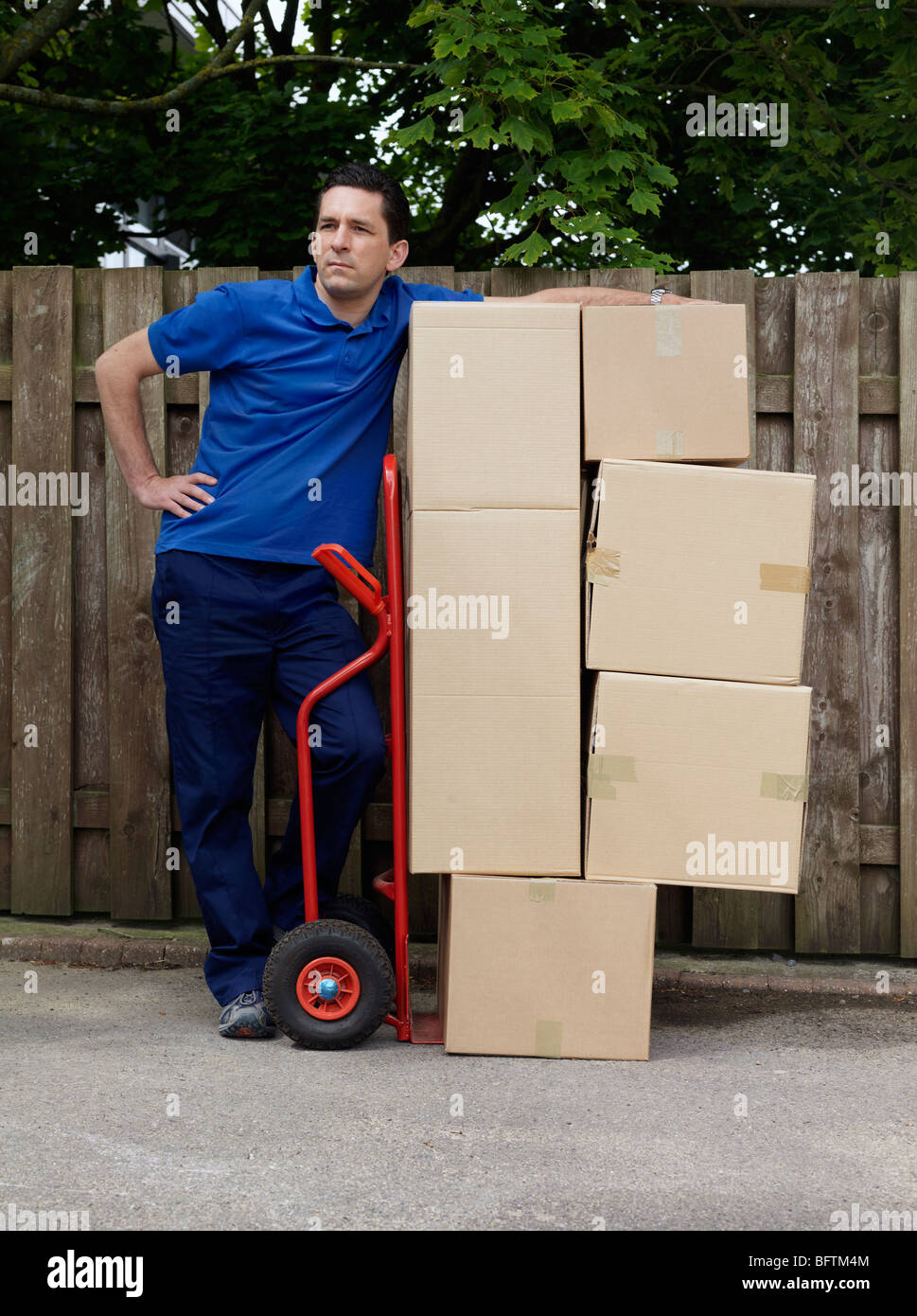 man delivering boxes on trolley - Stock Image