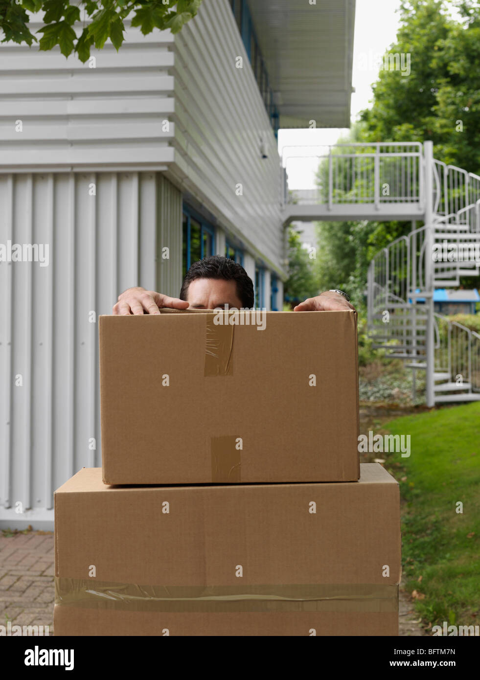 man with stack of boxes - Stock Image
