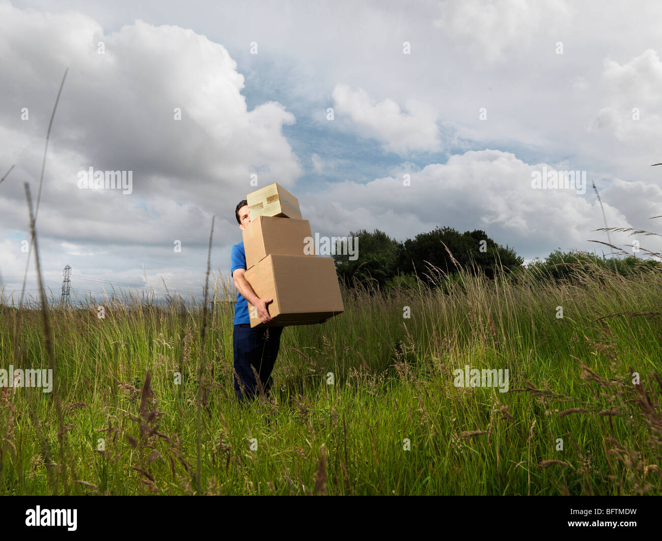 man carrying boxes through field - Stock Image