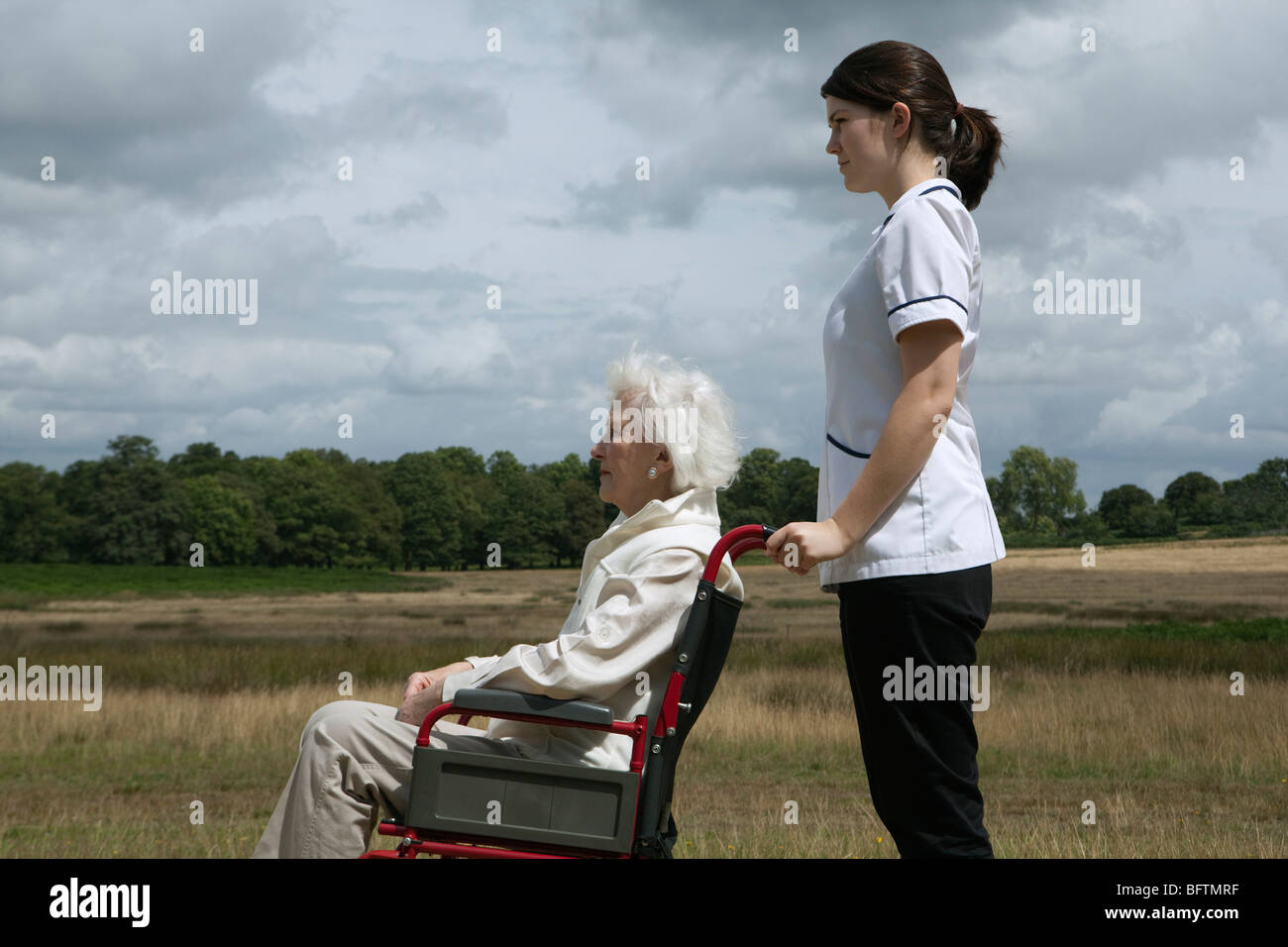 Elderly woman in wheelchair with nurse - Stock Image