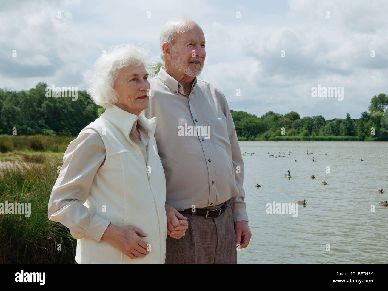 Elderly man holding elderly woman's hand - Stock Image