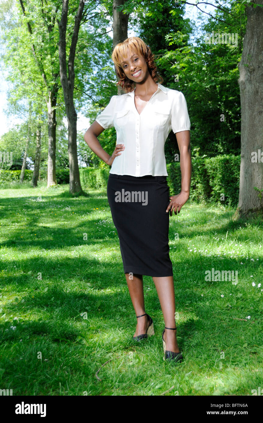 Young black fashion model, standing, smiling in smart formalwear in front of line of trees on a hot, sunny day. - Stock Image