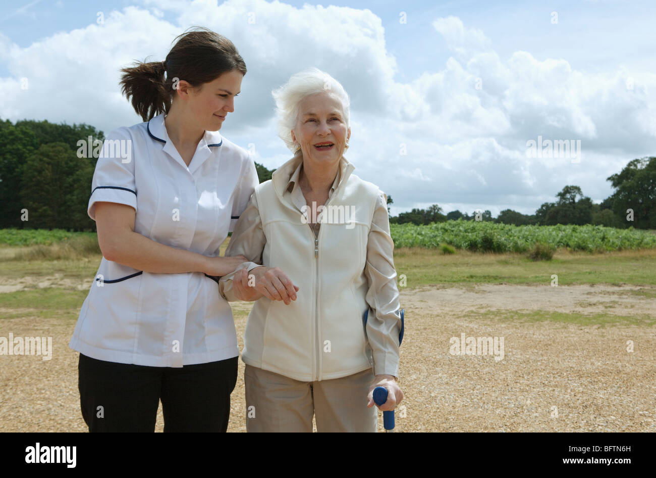 Elderly woman being supported by nurse - Stock Image