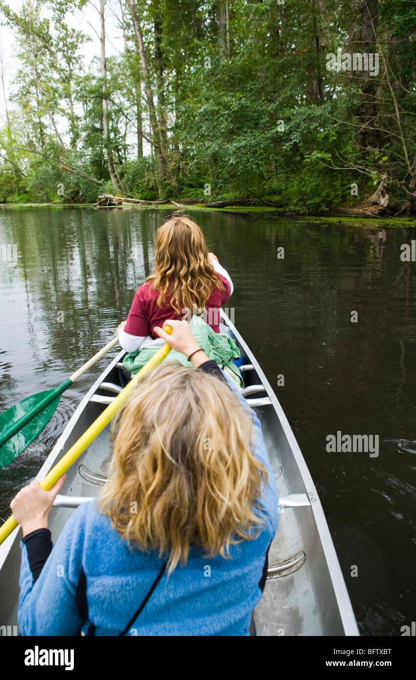Two women paddling a canoe in the Washington State University Arboretum in Seattle, Washington, USA. - Stock Image