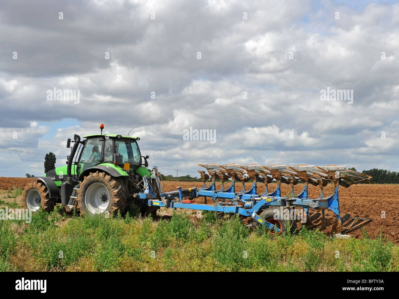 Green tractor ploughing a field ready for planting. - Stock Image
