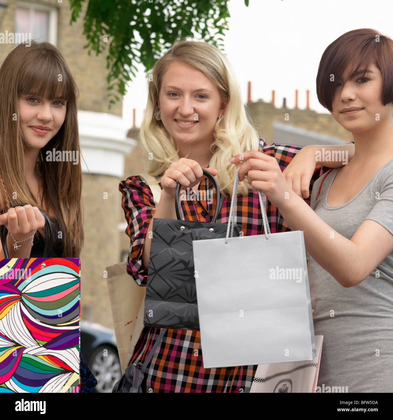 3 young women holding up bags - Stock Image