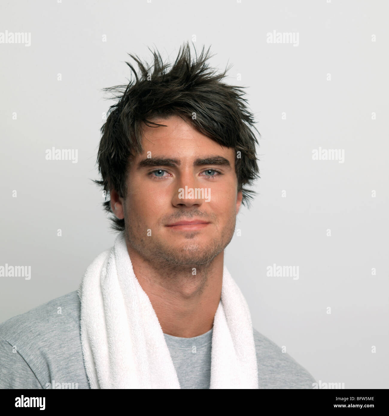 unshaved young man with towel - Stock Image