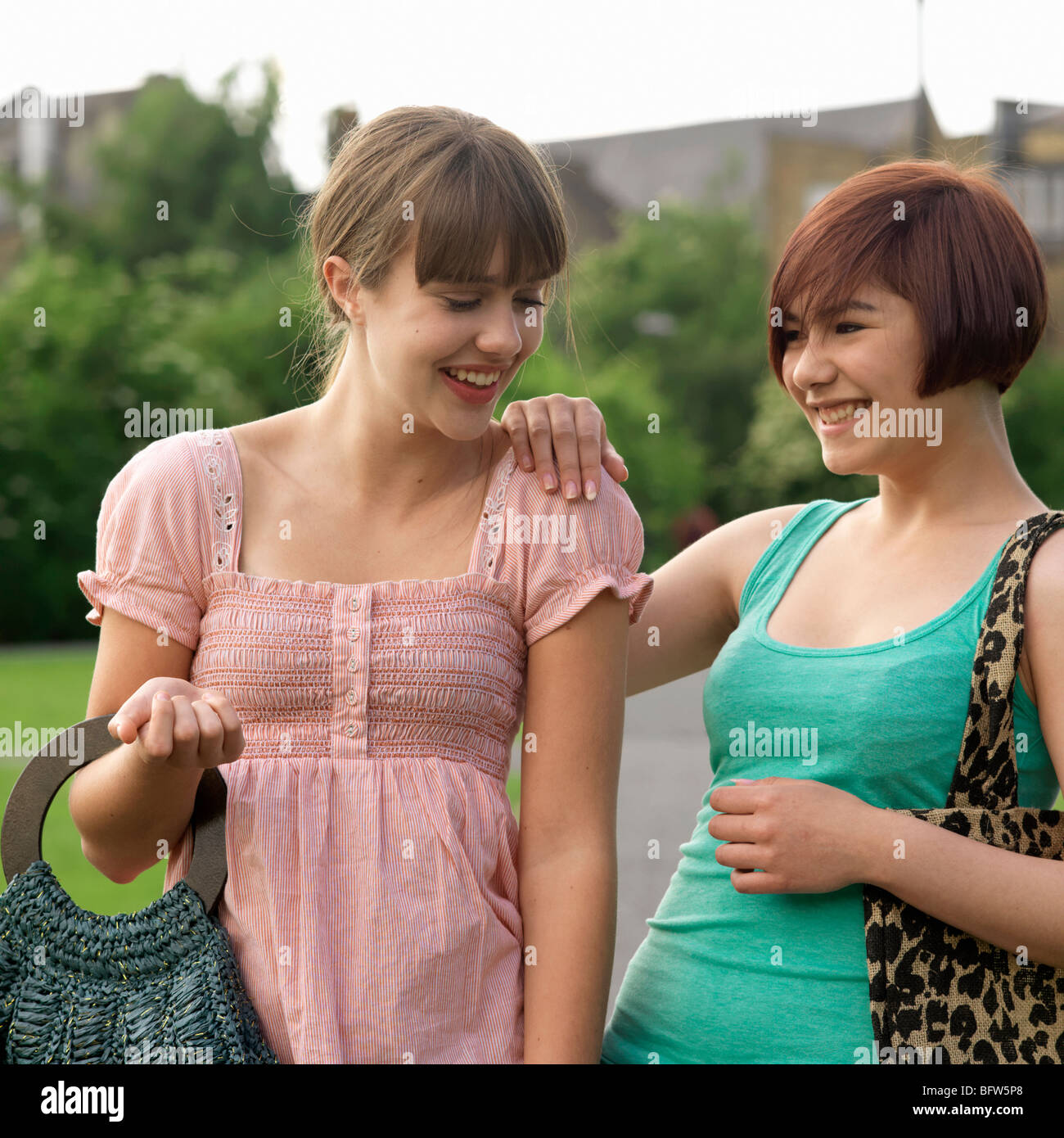 2 young woman laughing with bags - Stock Image