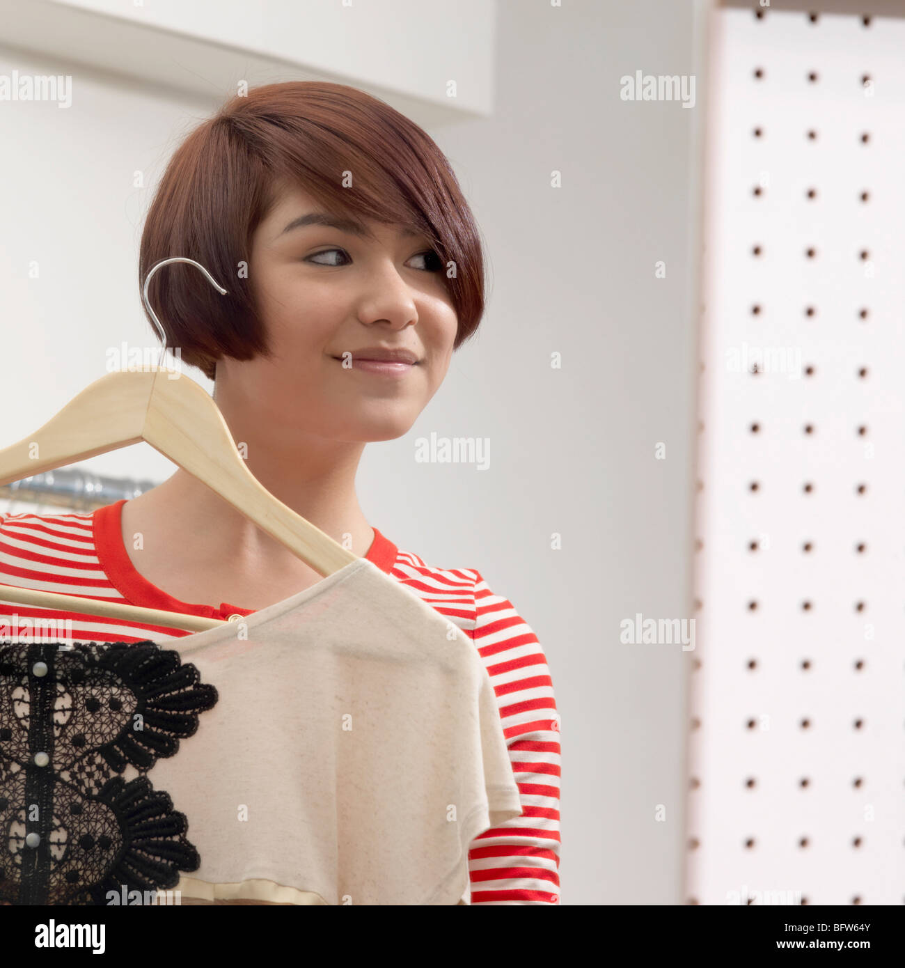 young woman holding an item of clothing - Stock Image