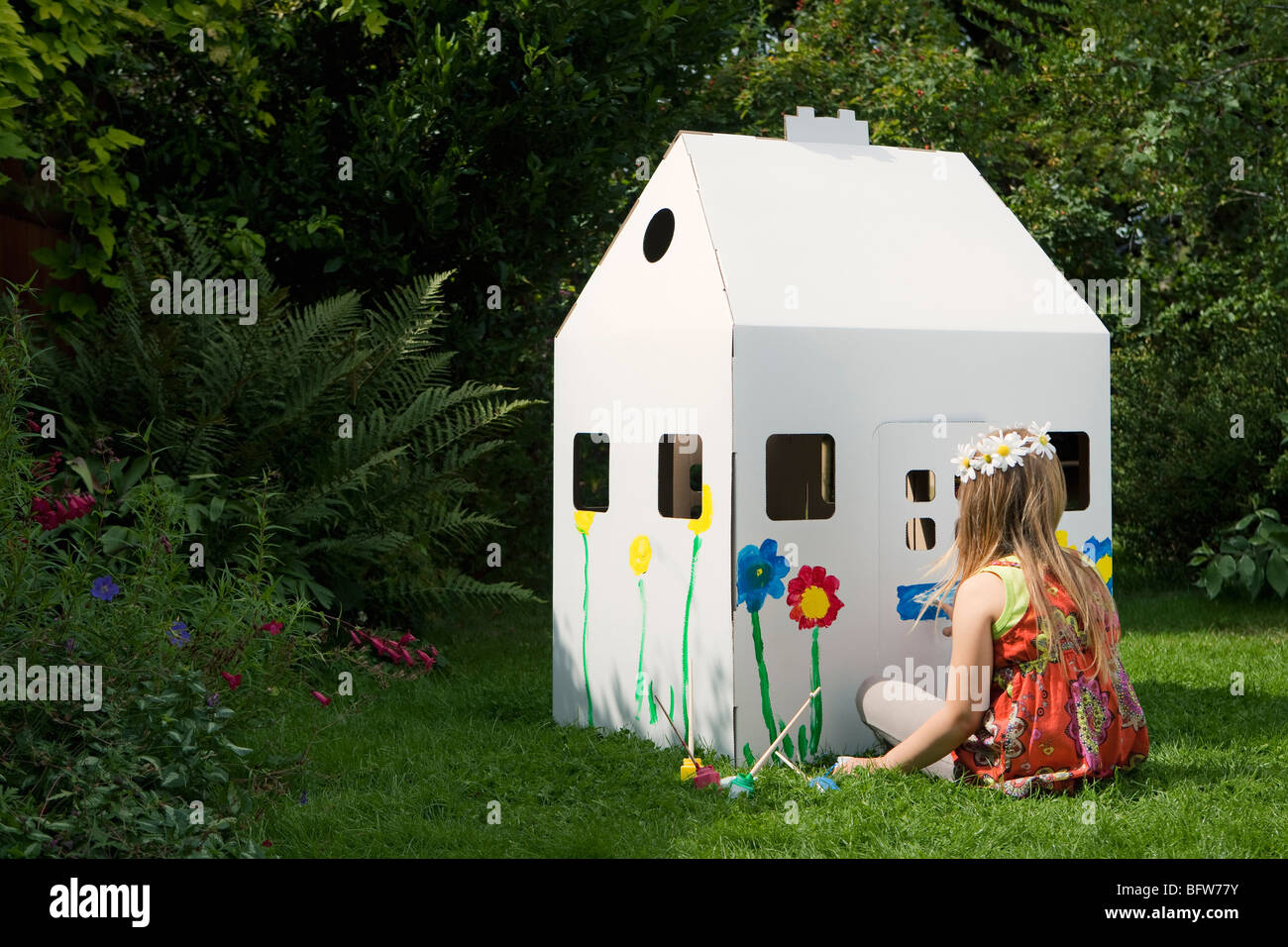 A girl painting a cardboard wendy house - Stock Image