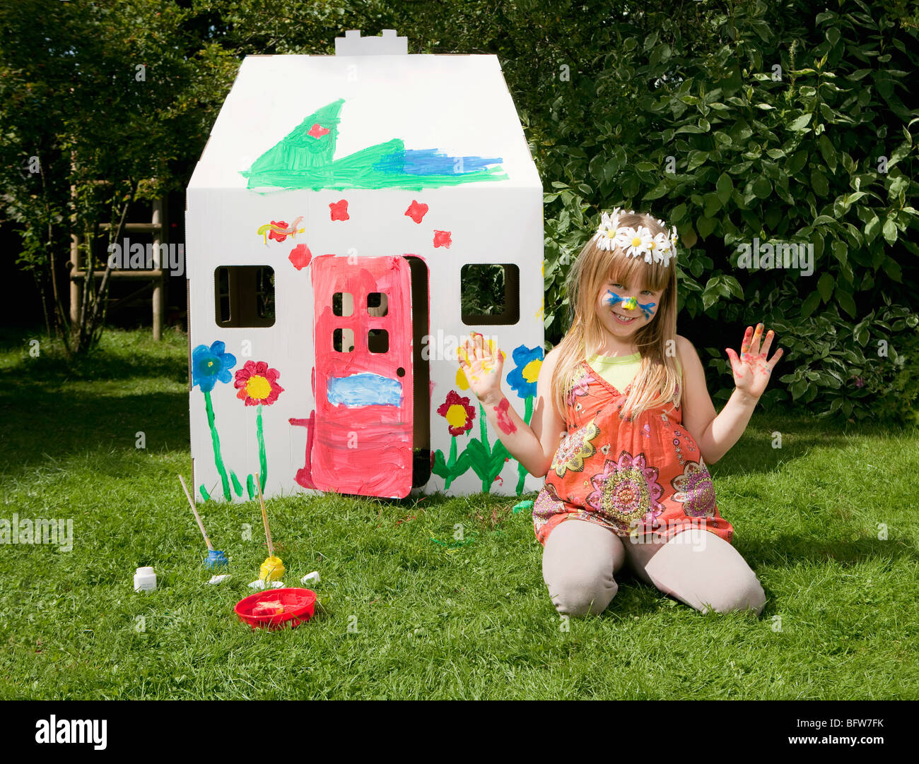A girl outside her painted wendy house - Stock Image