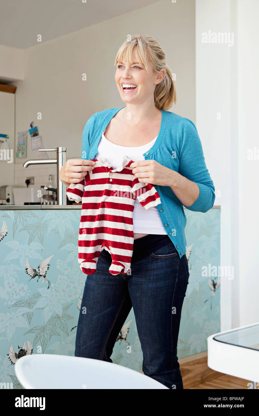 A young pregnant mum holding a baby grow - Stock Image