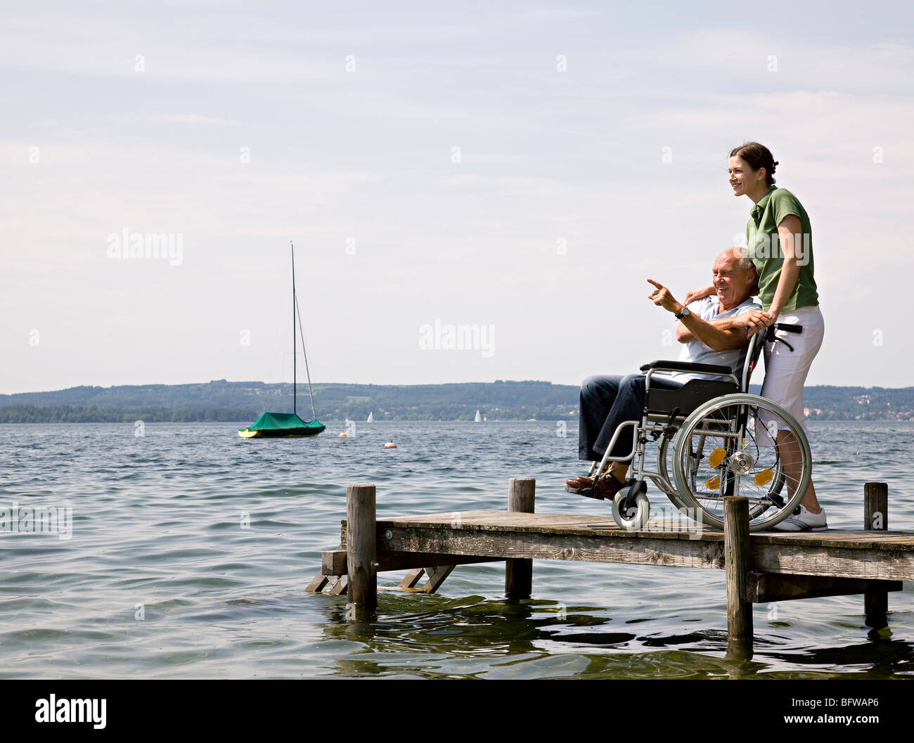 woman and senior man in wheelchair - Stock Photo