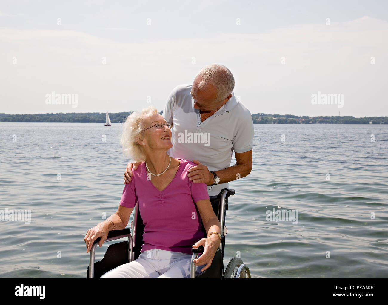 senior man and woman in wheelchair - Stock Photo