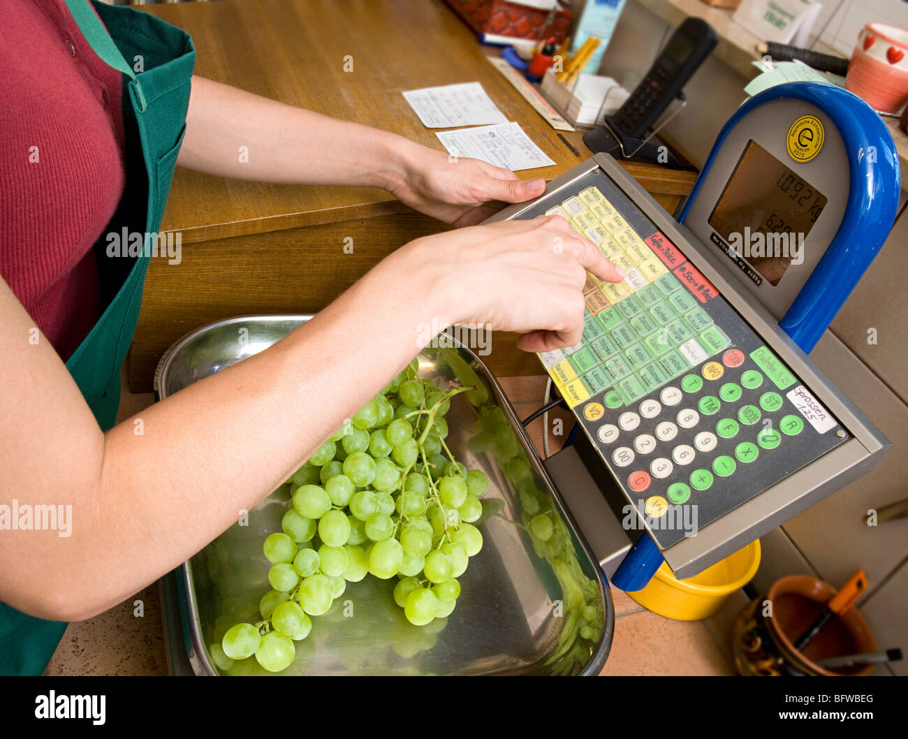 shopkeeper putting fruit on scale - Stock Image