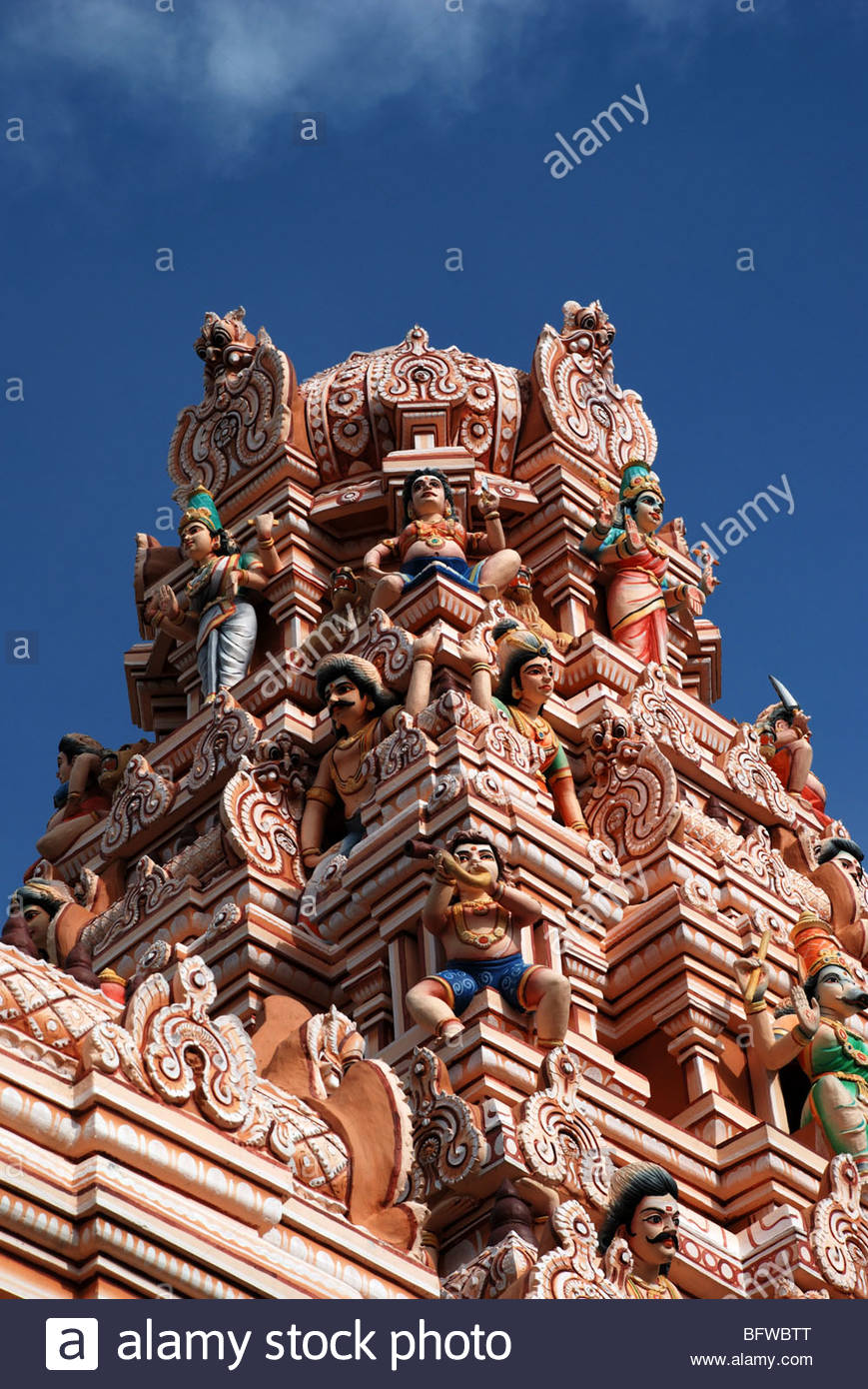 Small domed tower bedecked with numerous coloured statues of Hindu deities Rutra Viramuthu Maha Mariamman Hindu - Stock Image