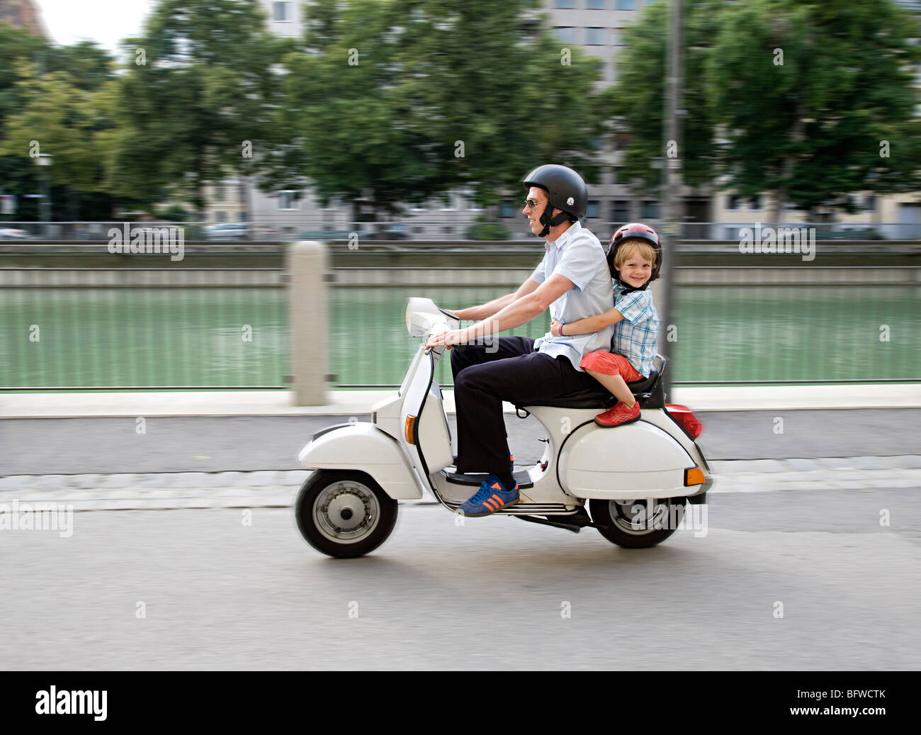 father and son on scooter - Stock Image