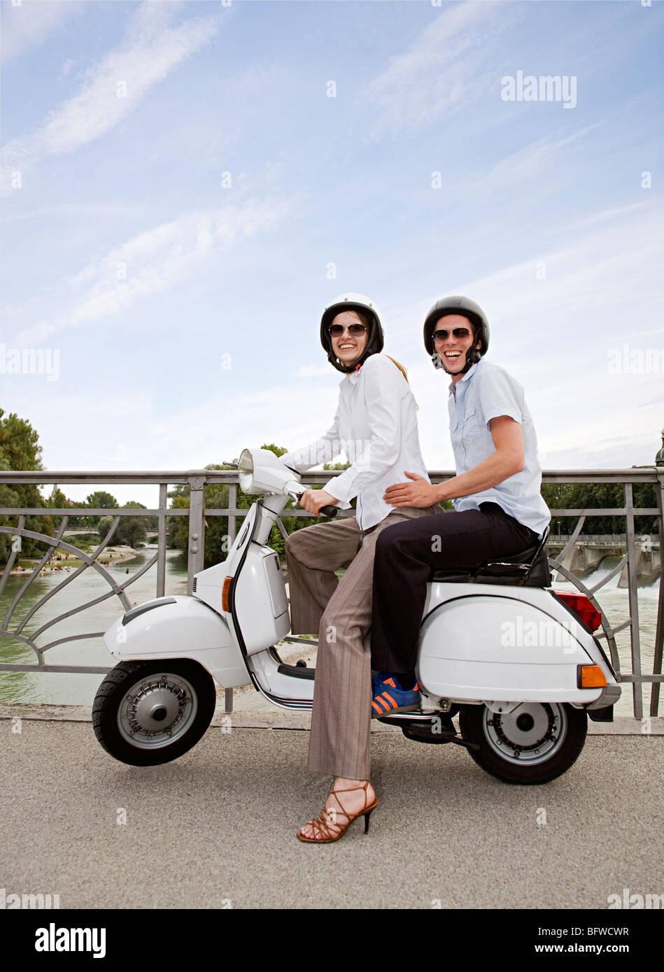 couple on scooter on bridge - Stock Image