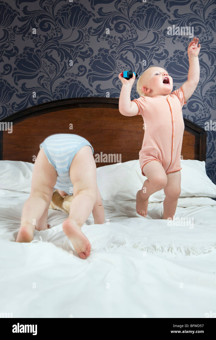 Two baby boys play on a bed Stock Photo
