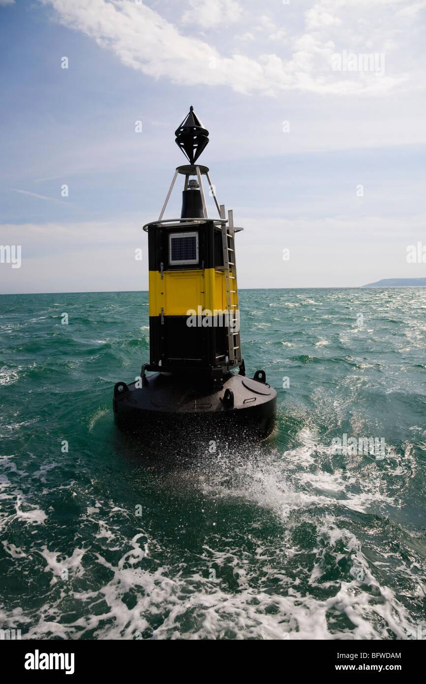 Wave splashing against buoy - Stock Image