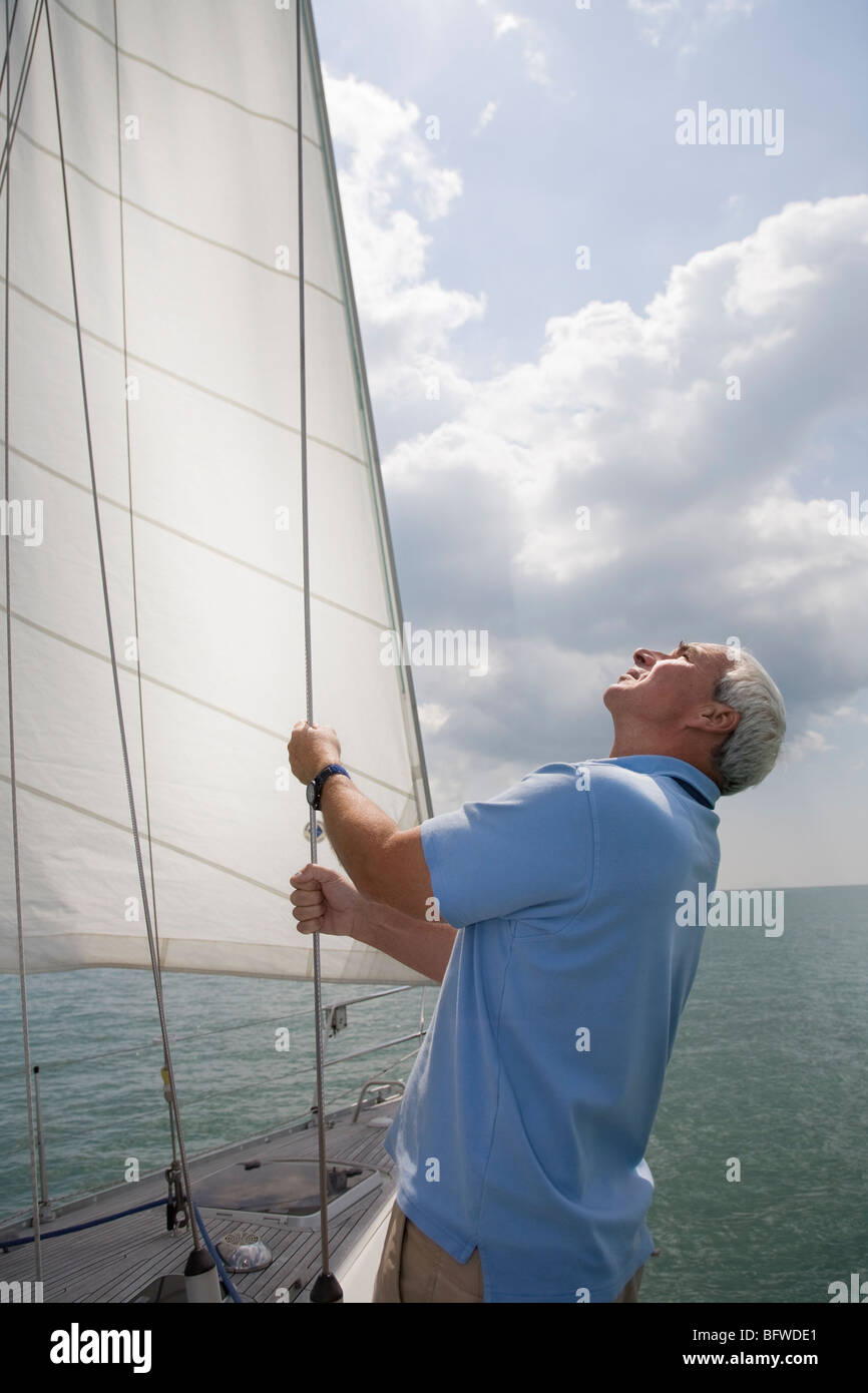Mature man checking sails on yacht - Stock Image