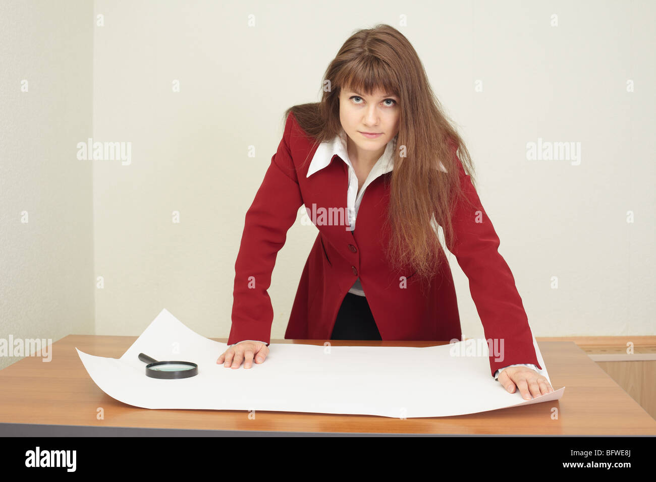 The young woman - the engineer works with the big drawing - Stock Photo