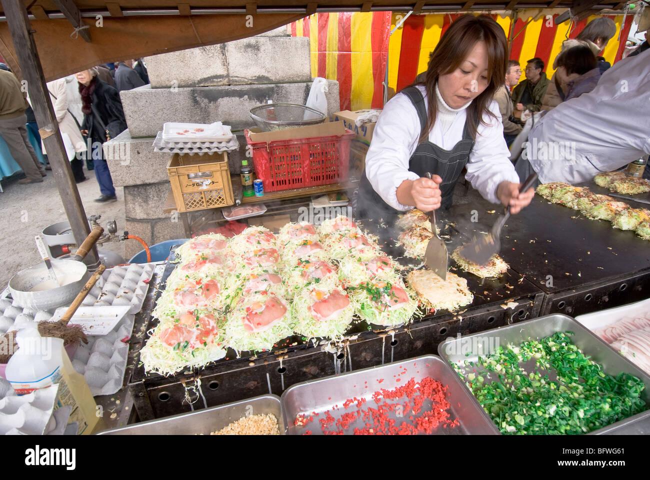 Japan, Kyoto, monthly Flea Market at Toji Temple, woman making japanese food Okonomiyaki Stock Photo