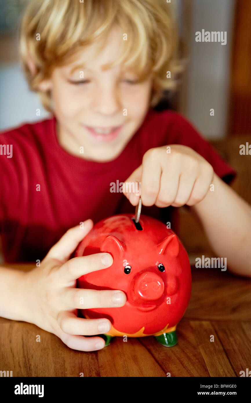 A boy putting money in a piggy bank - Stock Image