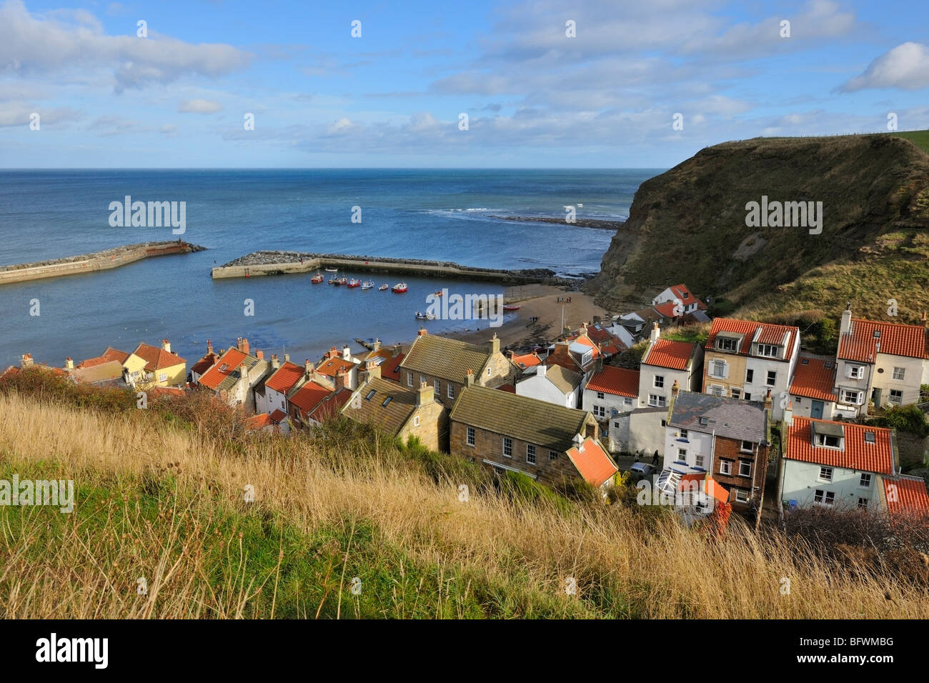 Hillside Cottages protected by Staithes Harbour, Yorkshire Heritage Coast, England - Stock Image