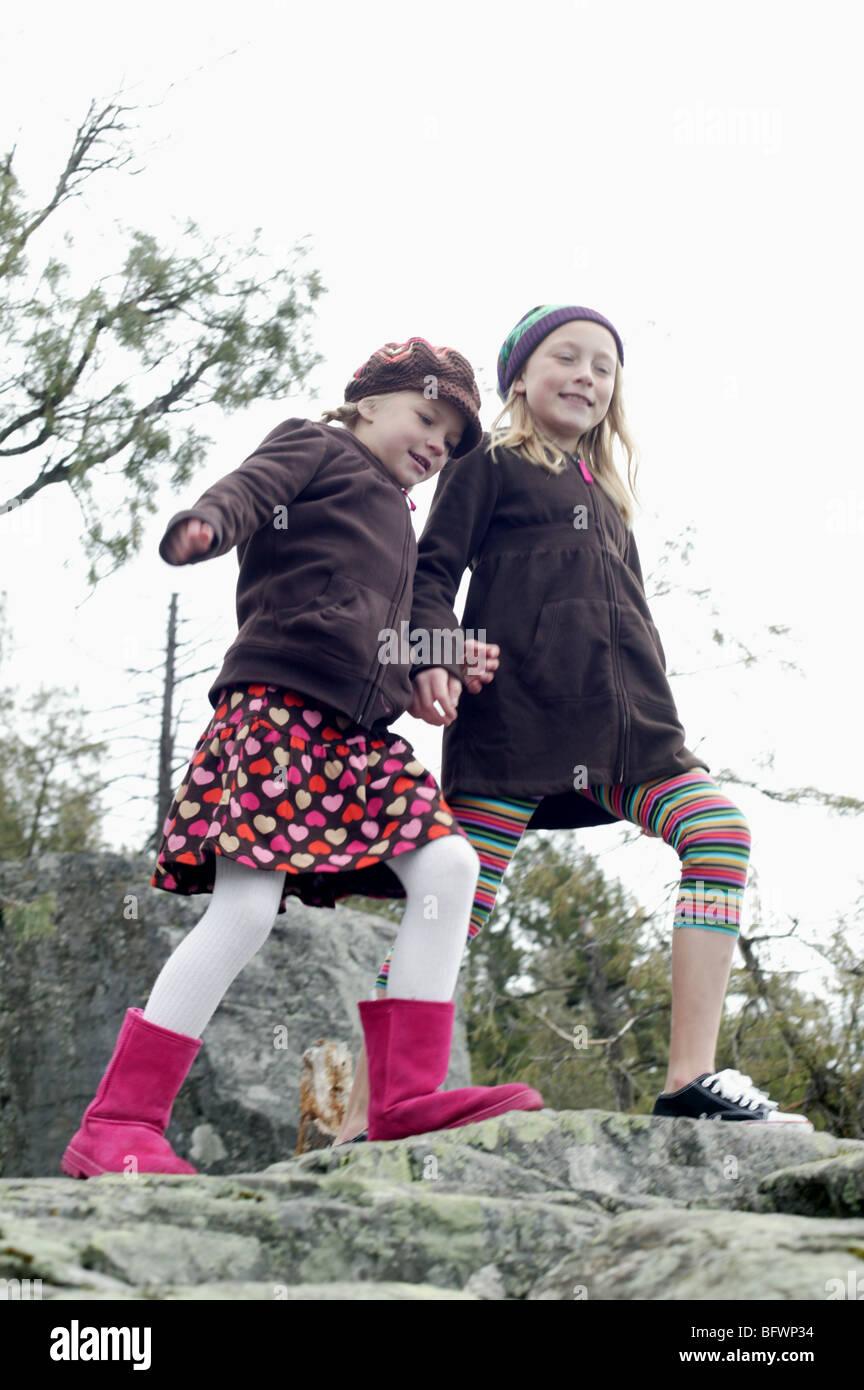 sisters walking on rocky lake shore - Stock Image