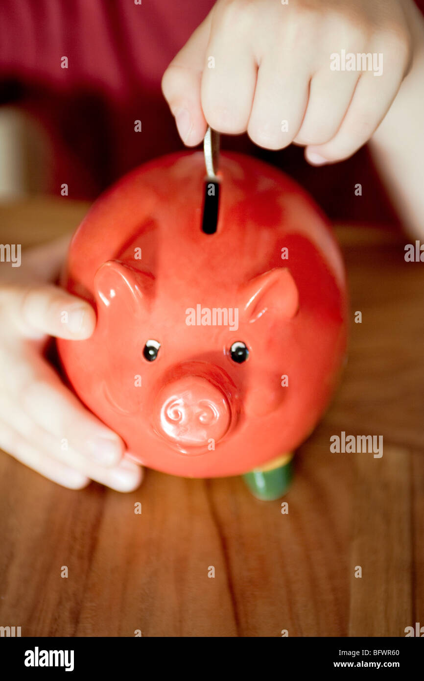 Money being put in a piggy bank - Stock Image