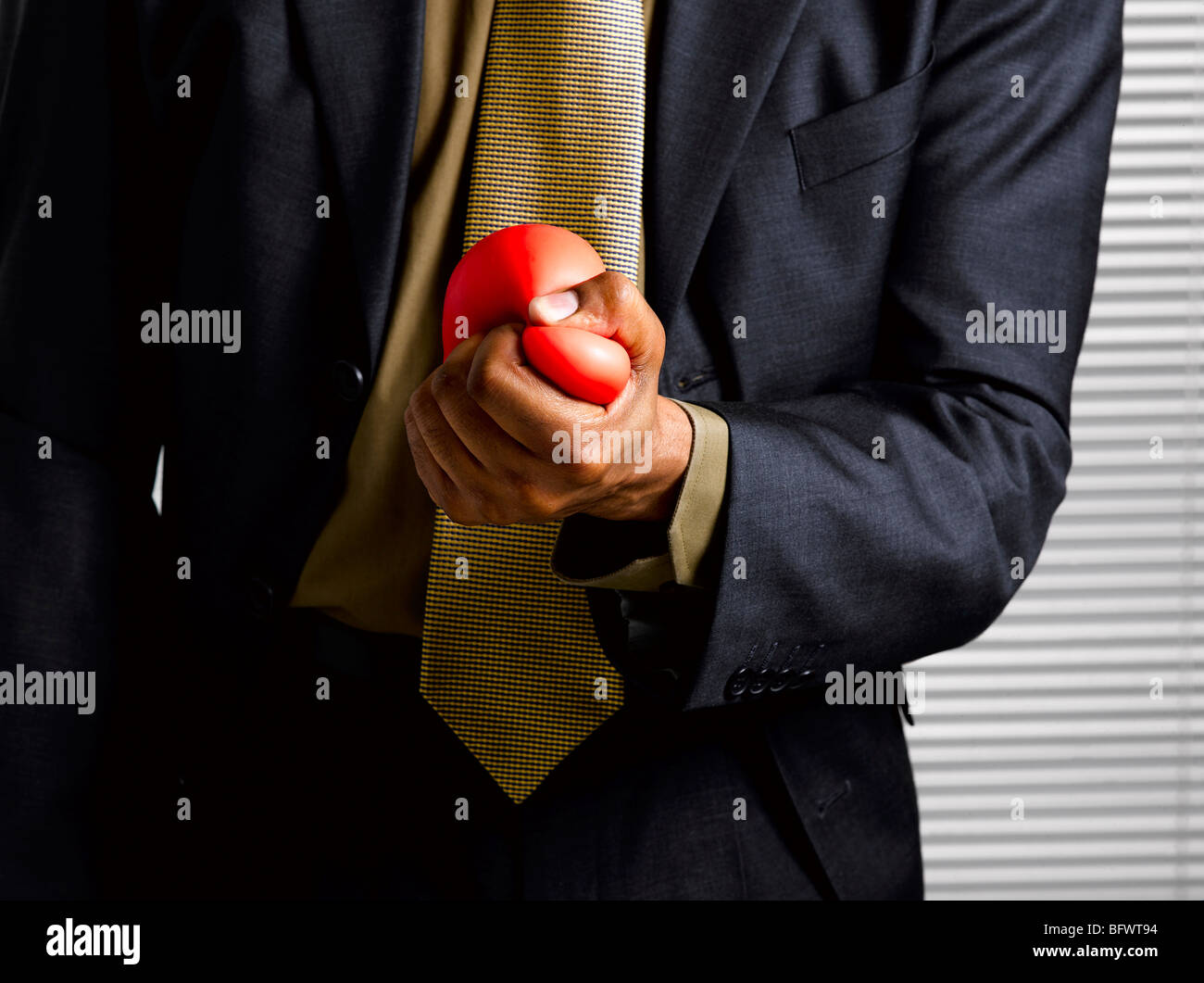Business man squeezing stress ball - Stock Image